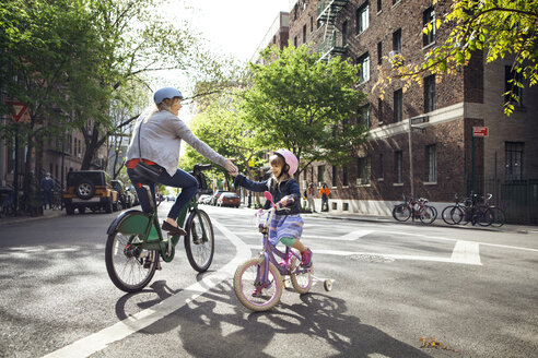 Mother and daughter giving high-five while riding bicycles on street - CAVF15958