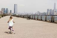 Rear view of girl cycling on promenade with city skyline in background - CAVF15970