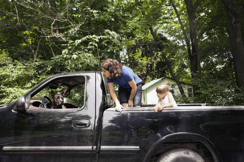 Sisters looking at dog in pick-up truck - CAVF15994