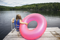Rear view of girl holding inflatable ring and sitting on pier - CAVF16003