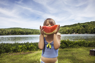Portrait of girl eating watermelon while standing at lakeshore - CAVF16006