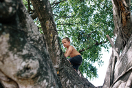 Low angle view of shirtless boy climbing tree at park - CAVF16021