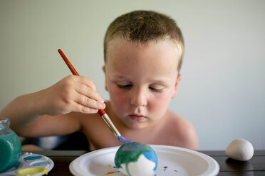 Shirtless boy coloring Easter egg while sitting by table at home - CAVF16027