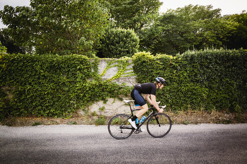 Side view of man cycling on road by ivy covered wall - CAVF16081