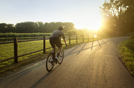 Male athlete cycling on road by field during sunny day - CAVF16123