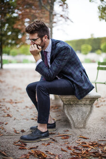 Thoughtful businessman sitting on park bench during autumn - CAVF16135