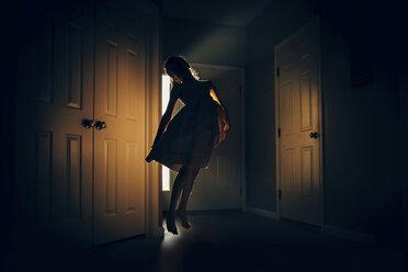 Happy girl jumping in darkroom at home - CAVF16201
