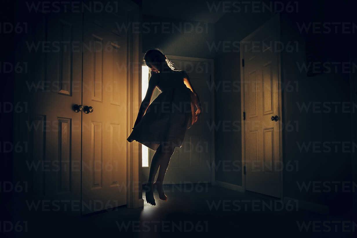 Happy girl jumping in darkroom at home - CAVF16201 - Cavan Images/Westend61