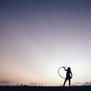 Silhouette girl playing with hula hoop against clear sky - CAVF16207
