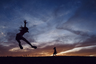 Silhouette sisters playing on field against dramatic sky during sunset - CAVF16216