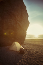 Tent by cliff on beach during sunset - CAVF16252
