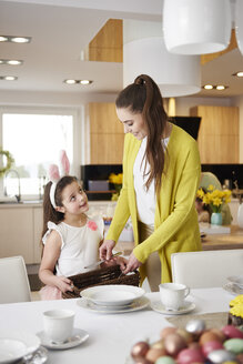 Smiling mother and daughter setting the table at home together - ABIF00149