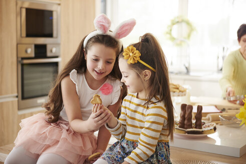 Two girls looking at cookie in kitchen - ABIF00152