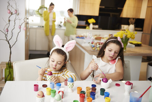 Sisters sitting at table painting Easter eggs - ABIF00173