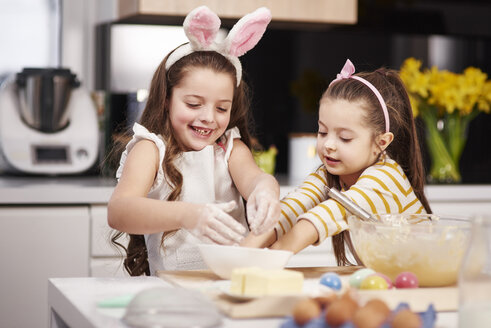 Two sisters having fun baking Easter cookies in kitchen together - ABIF00185