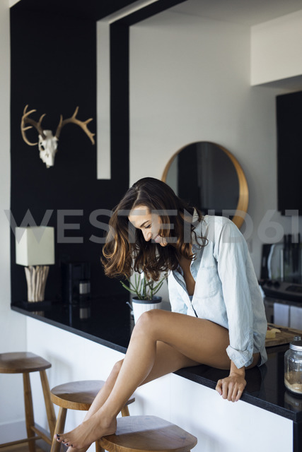 Smiling woman relaxing on kitchen counter - CAVF16318