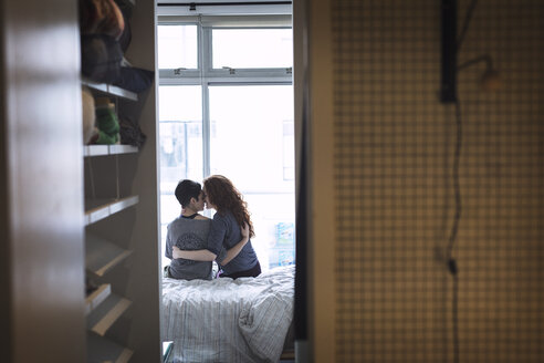 Romantic lesbian couple sitting on bed at home - CAVF16387