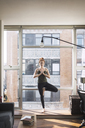 Woman practicing tree pose by window at home - CAVF16438