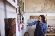 Artist looking paintings on wall in workshop - CAVF16465