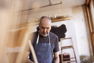 Senior male artist working in workshop - CAVF16480