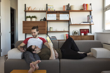 Homosexual couple relaxing on sofa at home - CAVF16501