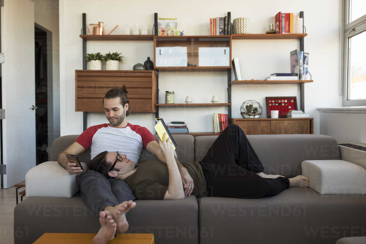 Homosexual couple relaxing on sofa at home - CAVF16501 - Cavan Images/Westend61
