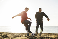 Playful father and son playing soccer at beach against clear sky during sunny day - CAVF16589