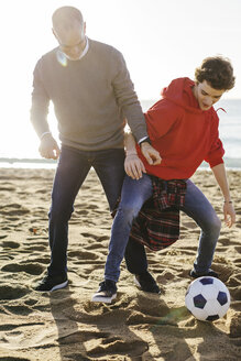 Full length of father and son playing soccer at beach during sunny day - CAVF16592