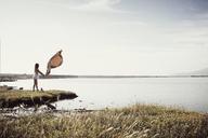 Woman spreading blanket at seashore - CAVF16622