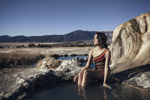 Thoughtful woman relaxing at Bridgeport Hot Springs against clear sky - CAVF16697