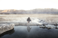 Woman touching water at Mammoth Lake Hot Springs against mountains - CAVF16703