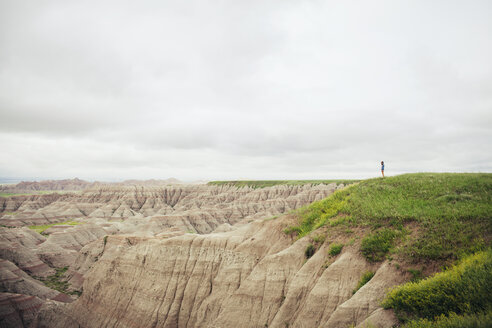 Woman standing on rock formation at Badlands National Park against cloudy sky - CAVF16742