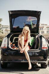 Portrait of confident woman sitting in car trunk on beach - CAVF16754