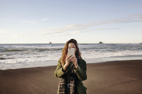 Young woman photographing through smart phone on beach - CAVF16766