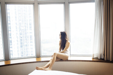 Thoughtful female tourist looking through window in hotel room in lingerie - CAVF16778