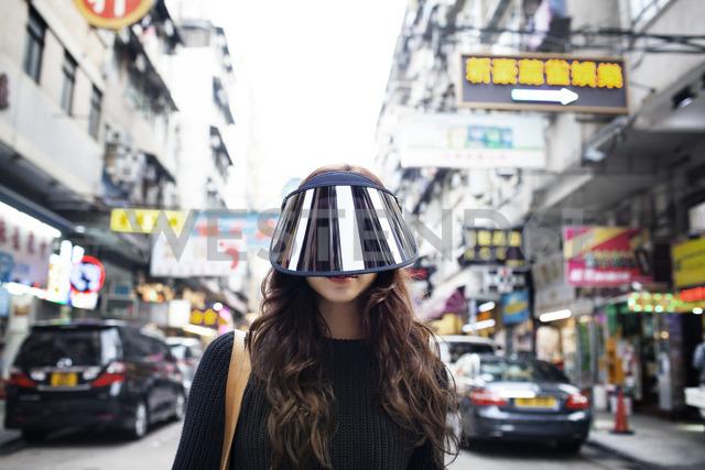 Portrait of female tourist wearing face visor on Hong Kong Street - CAVF16784