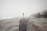 Side view of woman standing on cliff at beach during foggy weather - CAVF16871