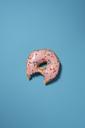 Overhead view of doughnut eaten bite on blue background - CAVF16934