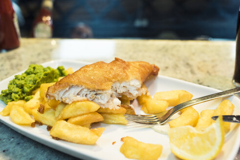 Close-up of fish with French fries and lemon slice in plate on table at restaurant - CAVF16943