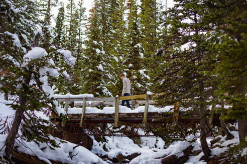 Low angle view of man walking on snow covered bridge amidst trees - CAVF16967