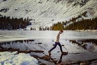 Man walking on rocks at frozen lake against mountain - CAVF16970