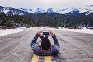 Man lying on street and photographing with smart phone against snowcapped mountains - CAVF16973