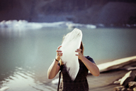 Woman holding ice and standing against lake - CAVF17003