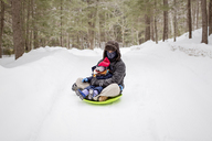 Father sitting with daughter on sled at snow covered field - CAVF17048