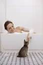Smiling woman stroking cat while bathing - CAVF17132