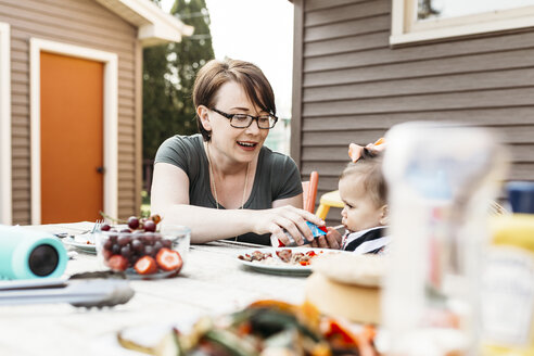 Mother feeding daughter while sitting at table in backyard - CAVF17276