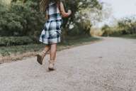 Low section of carefree girl running on dirt road - CAVF17312