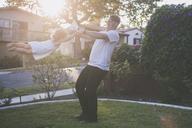 Happy father swinging daughter in backyard - CAVF17456