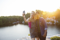Cheerful friends taking selfie through camera by lake during sunset - CAVF17651