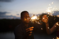 Friends holding sparklers at night - CAVF17663